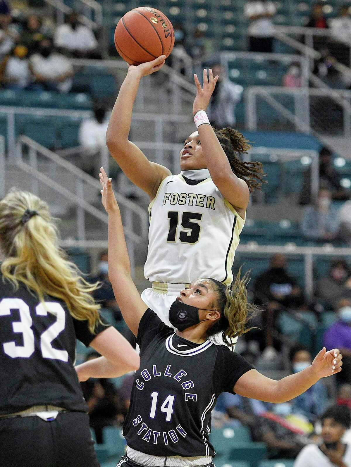 Foster guard Alicia Blanton (15) shoots over College Station guard Na'Layjah Johnson during the first half of a 5A Region III semifinal high school basketball playoff game, Friday, Feb. 26, 2021, in Katy, TX.