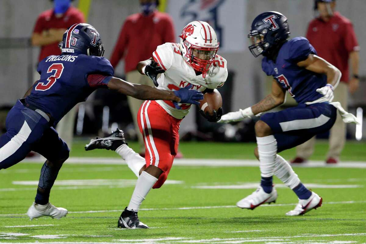 Katy's Seth Davis (23) runs between Tompkins defenders Temisan Alatan (3) and Dru Polidore, right, during the first half of a high school football game at Legacy Stadium Thursday, Nov. 5, 2020 in Katy, TX.
