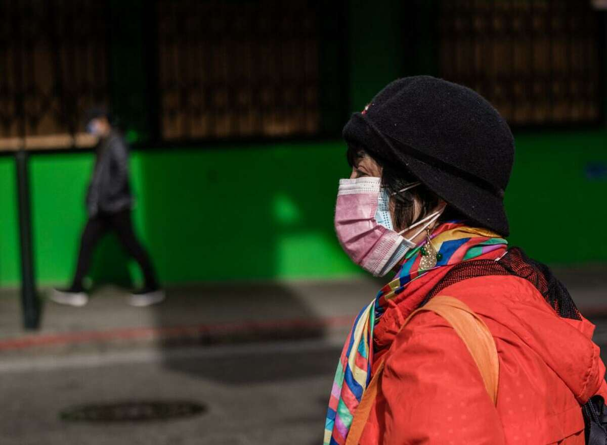 A woman wearing two masks is seen on the street in San Francisco on Thursday, January 21, 2021. As new variants of the Coronavirus reach the Bay Area, infectious disease experts have some tips on doubling down on mitigation measures.