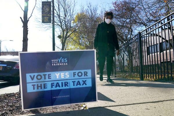 A woman walks past a pro-Fair Tax yard sign in November. Voters rejected the proposal to abolish Illinois' flat-rate income tax for one that would take a greater share from wealthier taxpayers.