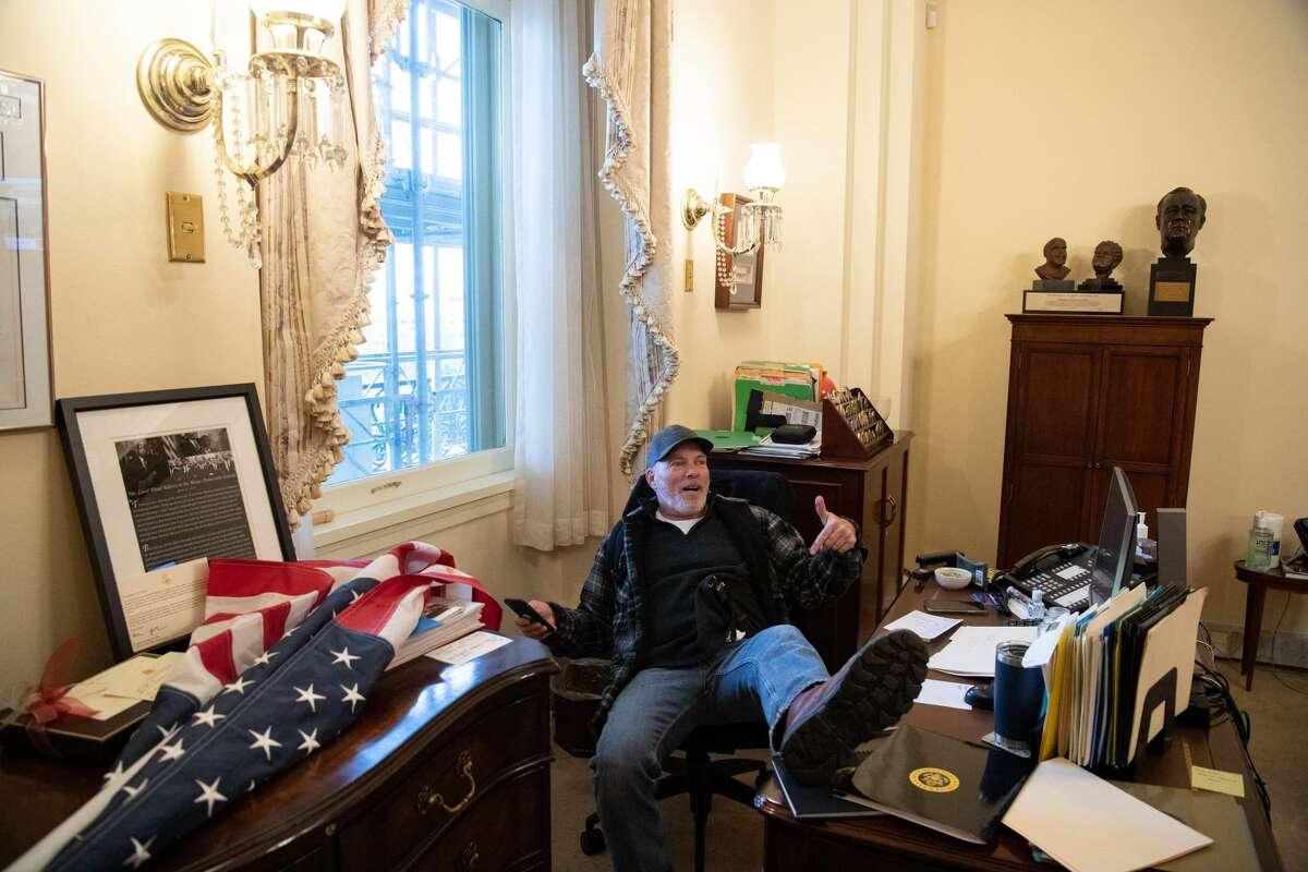 Richard Barnett, a supporter of US President Donald Trump, sits inside the office of US Speaker of the House Nancy Pelosi on January 6, 2021.