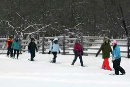 A Becoming an Outdoorswoman class enjoys snowshoeing on aFebruary afternoon at the Bay Cliff Health Camp in Marquette County. (Courtesy/Michigan DNR)