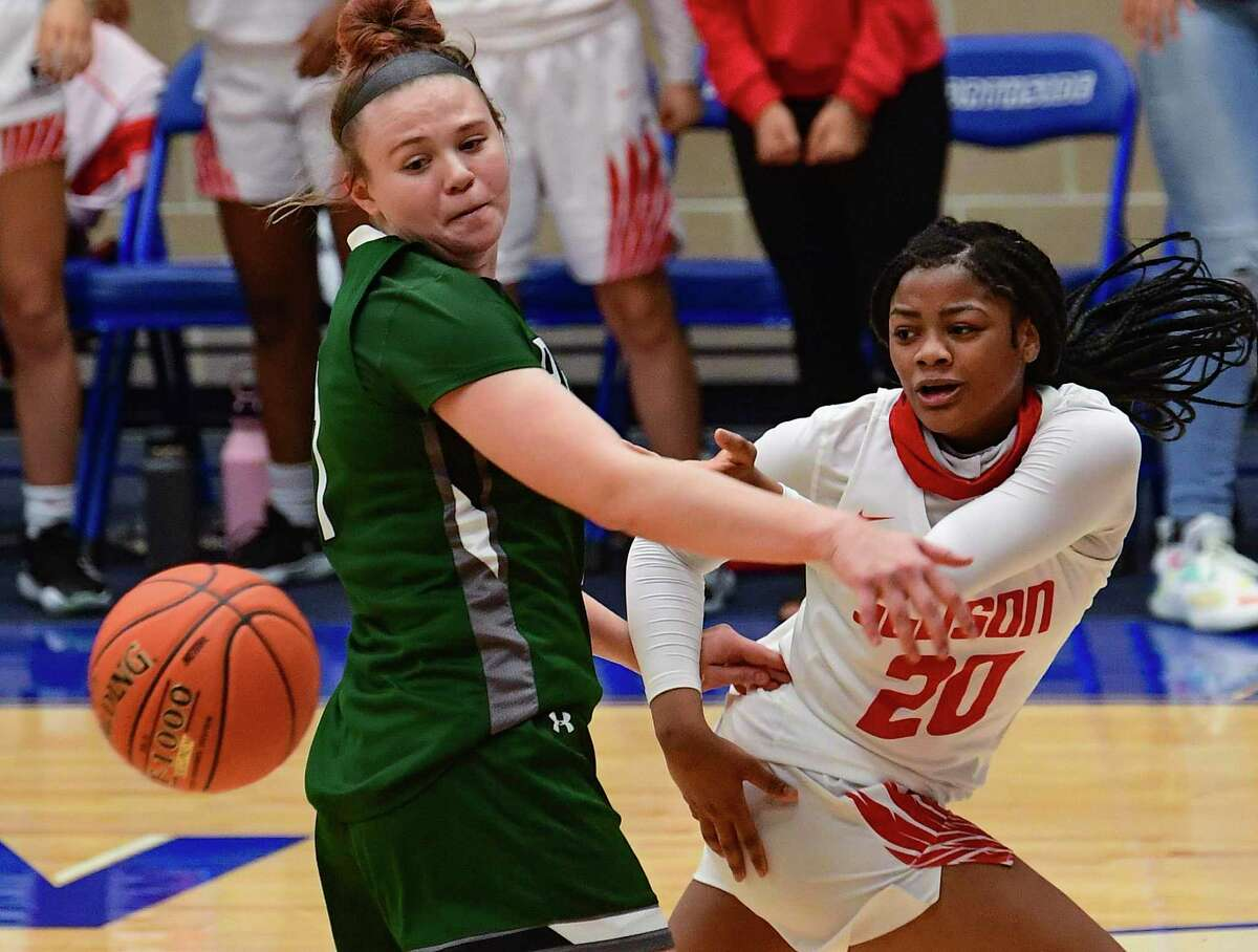 Kierra Sanderlin (20) of Judson passes the ball behind Samantha Wagner of Reagan during second-half action of the girls basketball Region IV-6A Regional Championship game at the Northside Sports Gym on Tuesday, March 2, 2021.