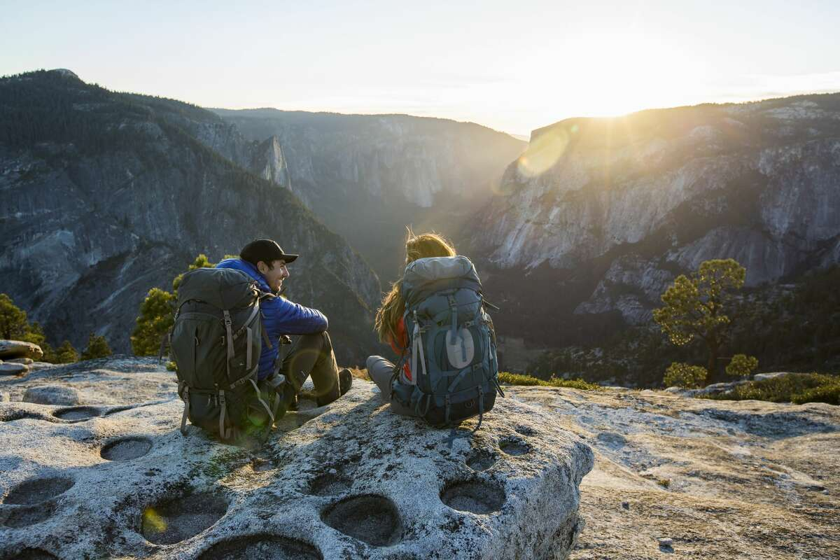A couple sitting on a ledge while backpacking in Yosemite Valley.