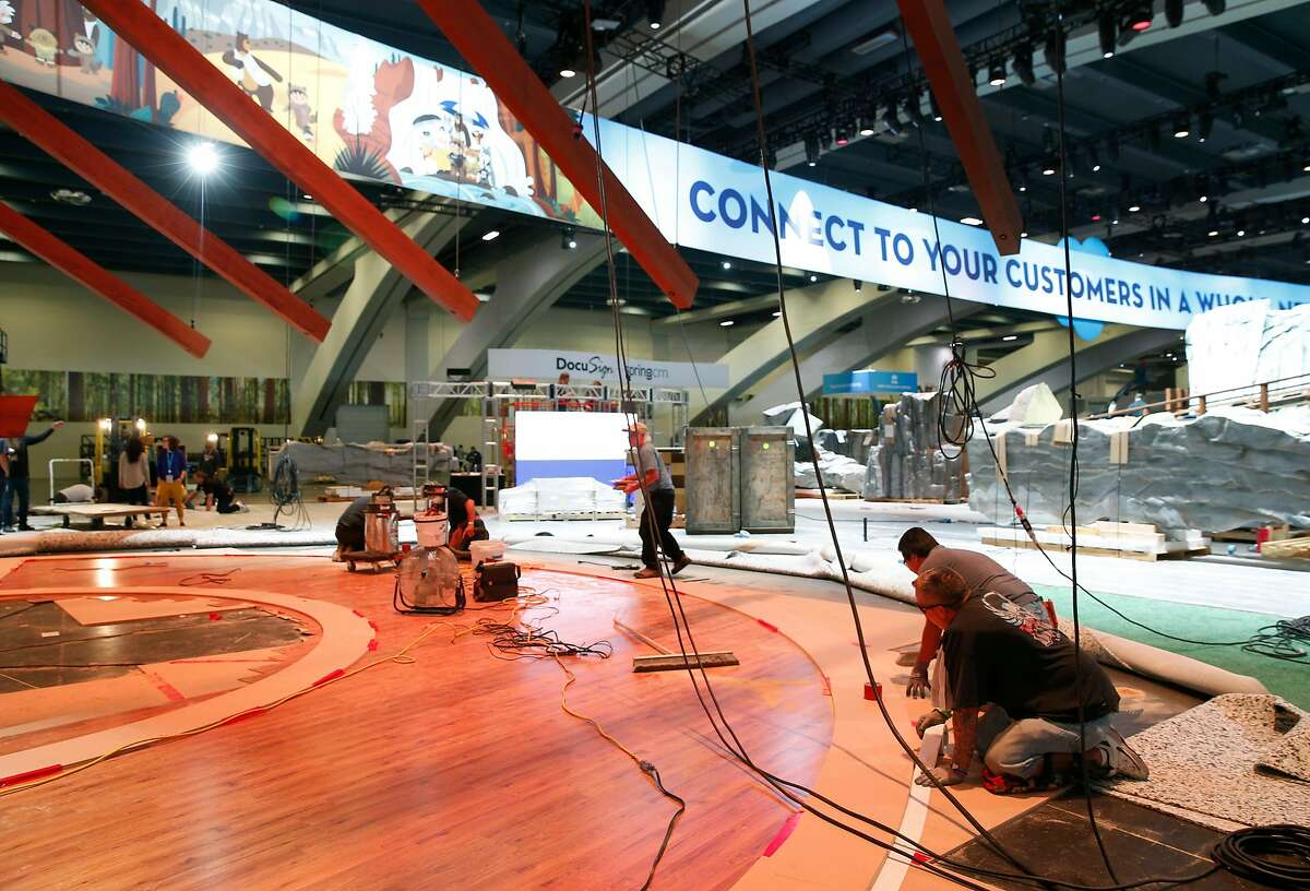 An installation crew assembles a display inside a conference at Moscone Center in 2018. Representatives of California's tourism industry are seeking guidance from Gov. Gavin Newsom on when conventions may resume.