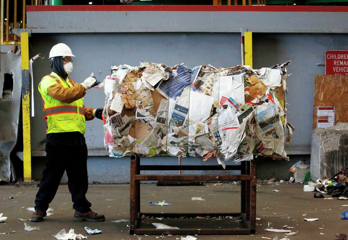 Recology materials Handler Allen Maculangan removes plastic bags from bales of paper in 2019.