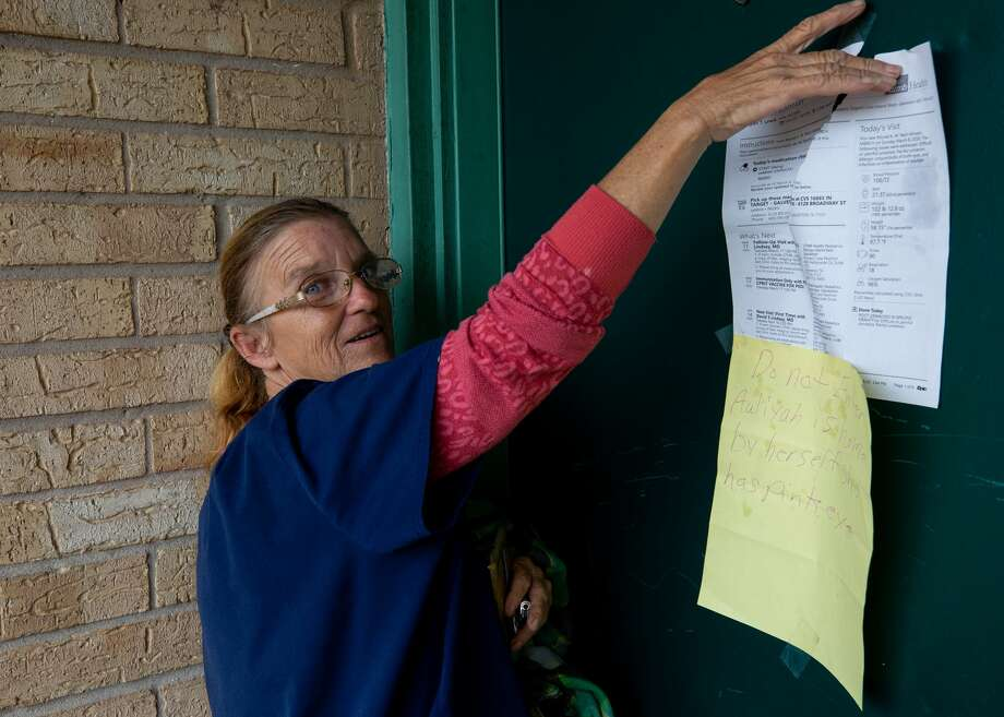 Tina Harris tapes the latest report from her daughter's hospital visit on their apartment door. Photo: Godofredo A. Vásquez/Staff Photographer / ? 2020 Houston Chronicle