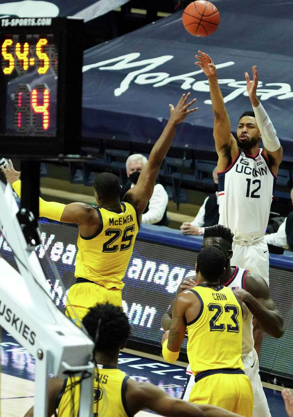 UConn's Tyler Polley (12) shoots a 3-pointer against Marquette in Storrs.