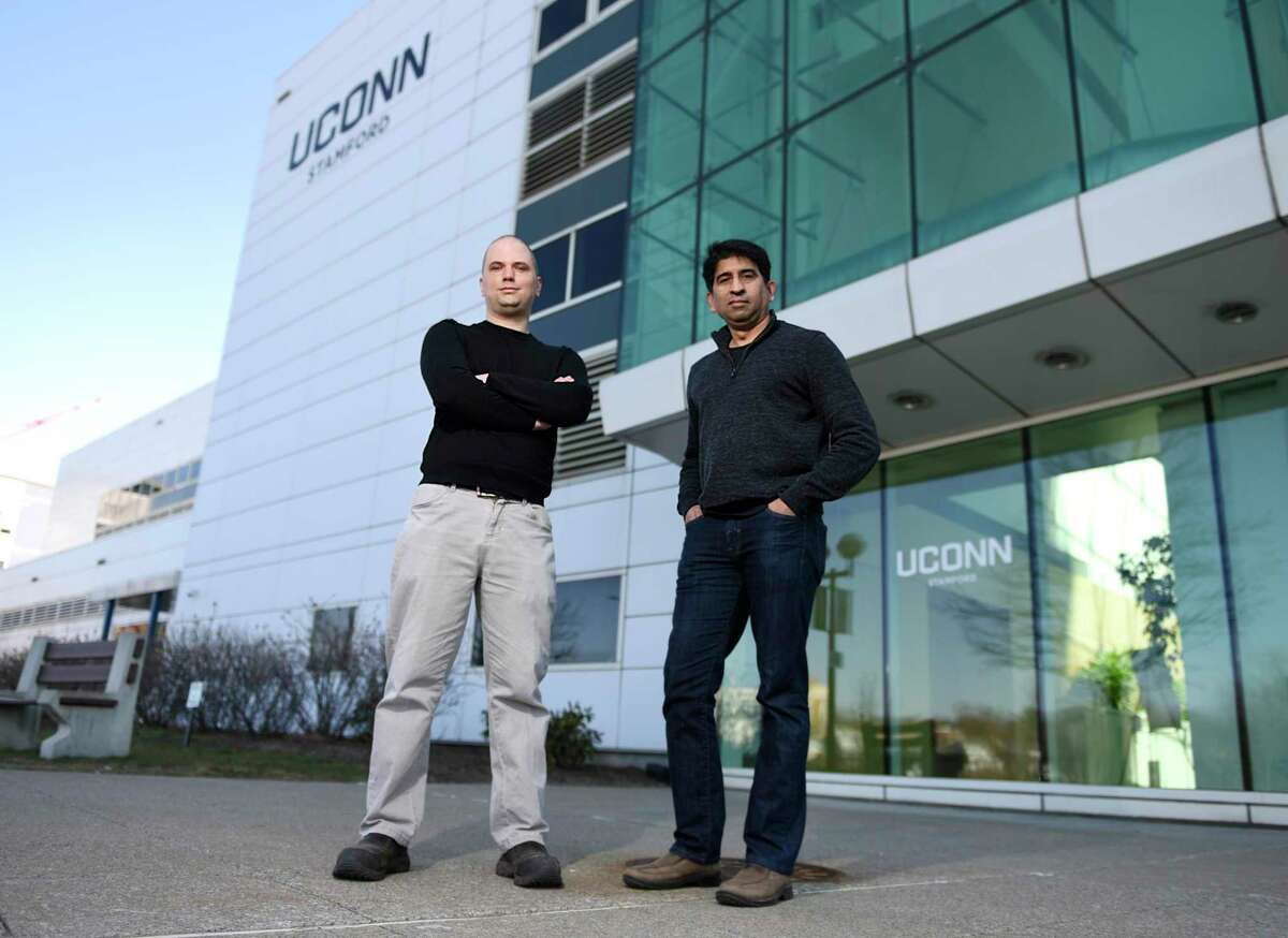 ACW Analytics Chief Technology Officer Peter Watson, left, and CEO Vijay Jayachandran pose at the corner of Washington Boulevard and Broad Street, outside the University of Connecticut's main academic building, in Stamford, Conn., on Wednesday, March 3, 2021. ACW Analytics is one of the companies participating in UConn's Technology Incubation Program in Stamford.