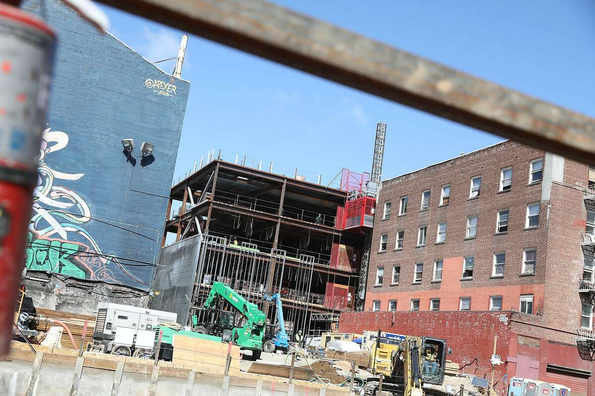 The plumbers union hall is under construction, flanked by the existing one (left) and the Civic Center Navigation Center.