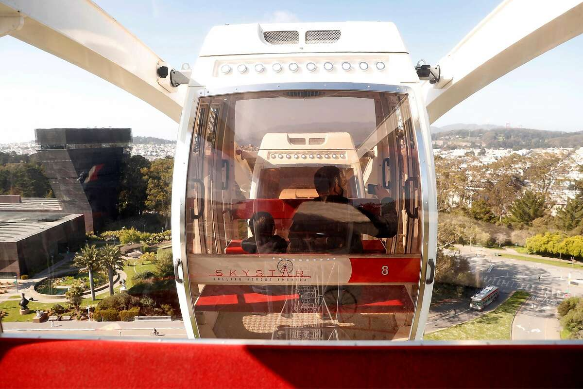 Ash Holmes and his son, Alex, take in the panoramic view of San Francisco in a gondola at the top of the Ferris wheel on Thursday.