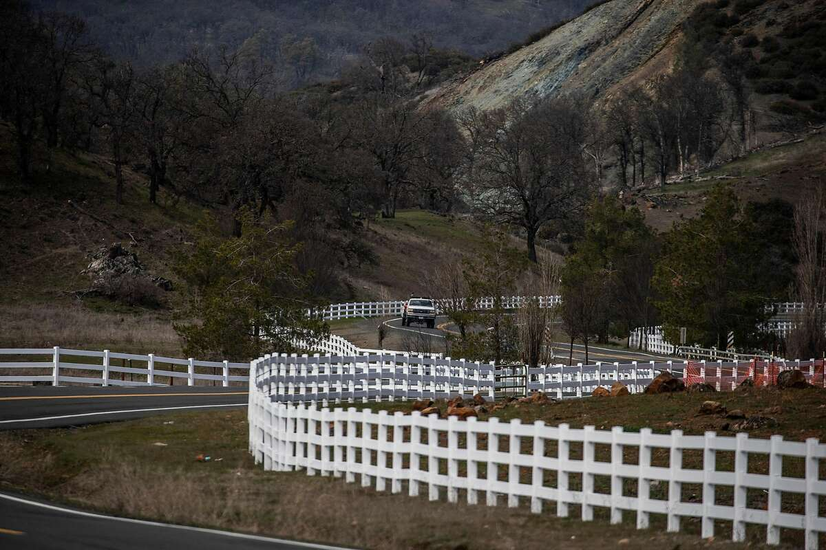 White fencing runs along Butts Canyon Road in Middleton, where a development is being considered that would include 1,400 homes. The site's Guenoc Valley location is considered a high-risk zone for wildfires.