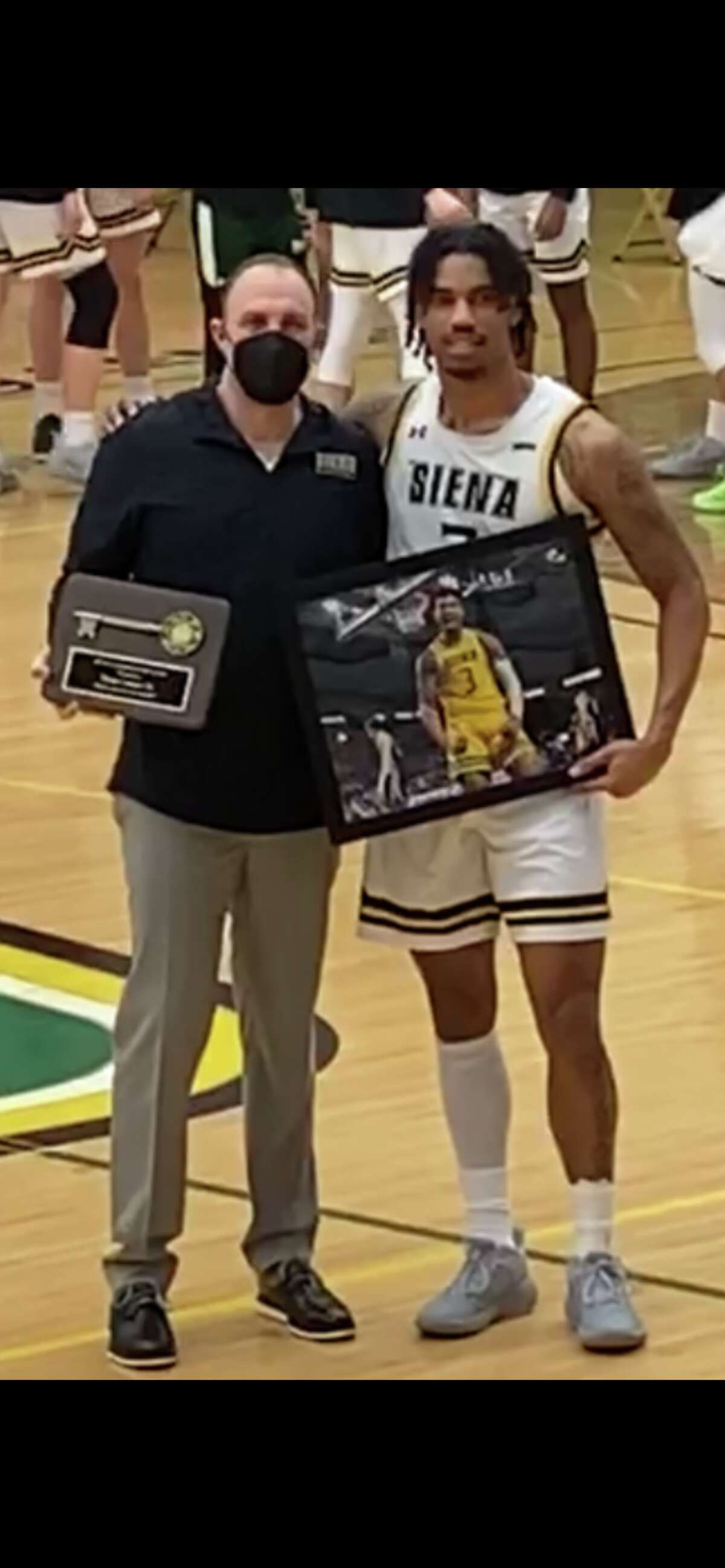 Siena guard/forward Manny Camper, pictured along head coach Carmen Maciariello, was honored on Senior Night before Thursday's game against Canisius. Camper said he hasn't decided whether he'll return to the Saints for a fifth year. (Mark Singelais/Times Union)