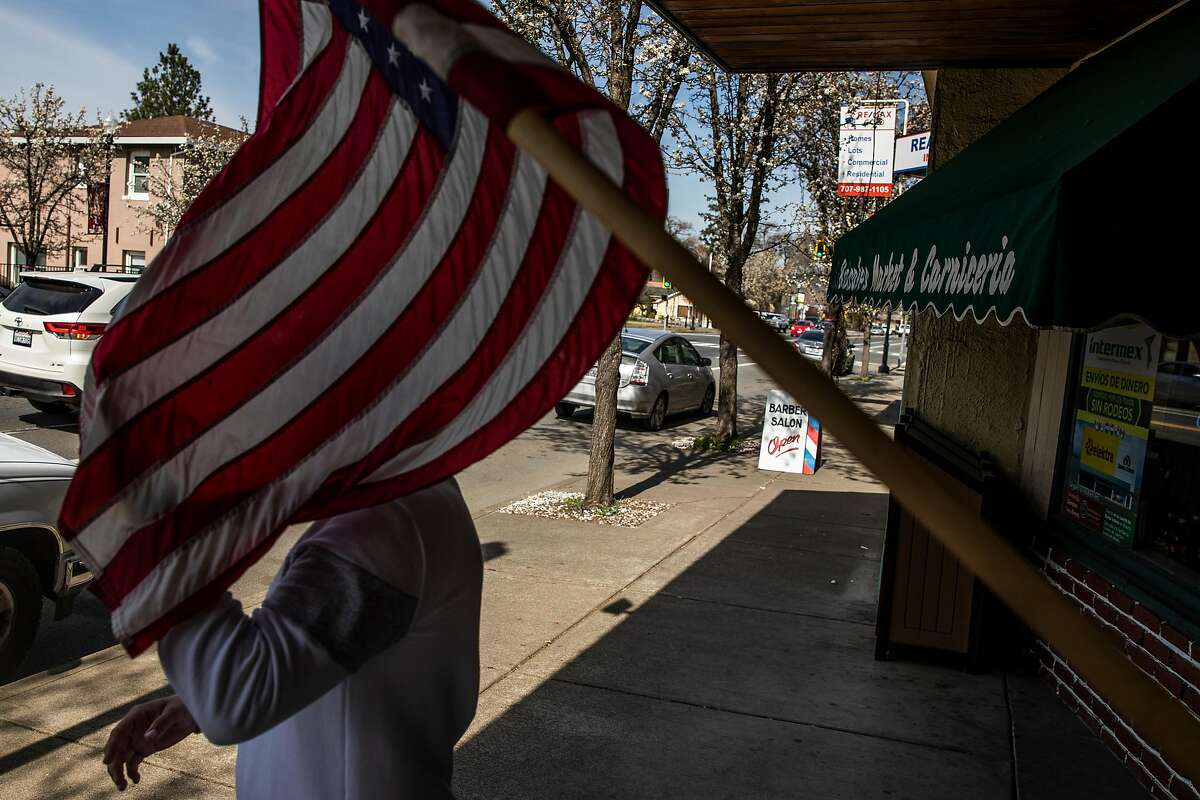 A man touches a U.S. Flag outside the Rosales Market in Middletown (Lake County) on March 3, 2021.