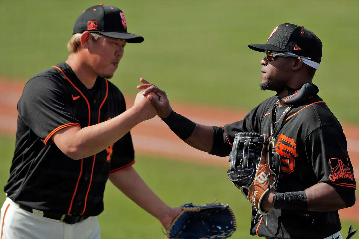 Shun Yamaguchi (1) thanks Luis Basabe (53) for his catch that saved two runs in the fifth inning as the San Francisco Giants played the Chicago White Sox in a spring training game at Scottsdale Stadium in Scottsdale, Ariz., on Thursday, March 4, 2021.