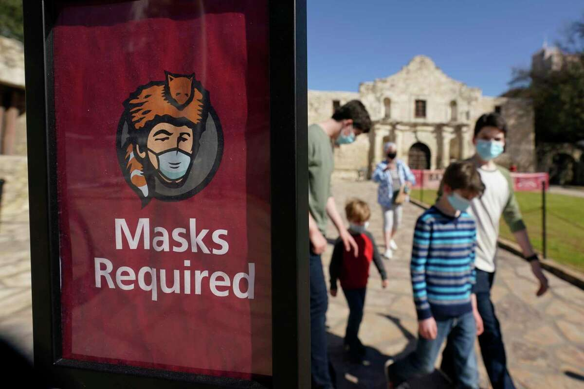 Visitors wearing face masks leave the Alamo on Wednesday, March 3, 2021, in San Antonio. Gov. Greg Abbott says Texas is lifting a mask mandate and lifting business capacity limits next week.