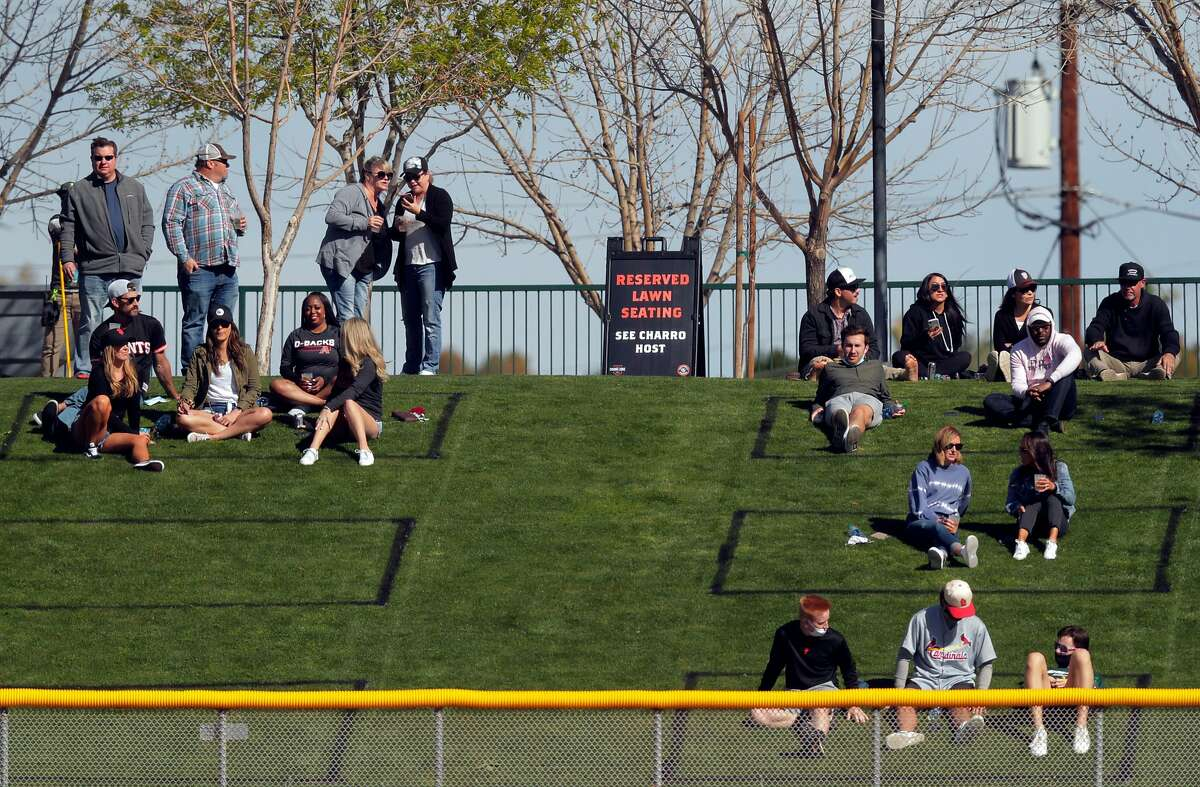 Fans watch from the grass in reserved, sectioned off segments of the lawn as the San Francisco Giants played the Los Angeles Angels at Scottsdale Stadium in Scottsdale, Ariz., on Sunday, February 28, 2021.
