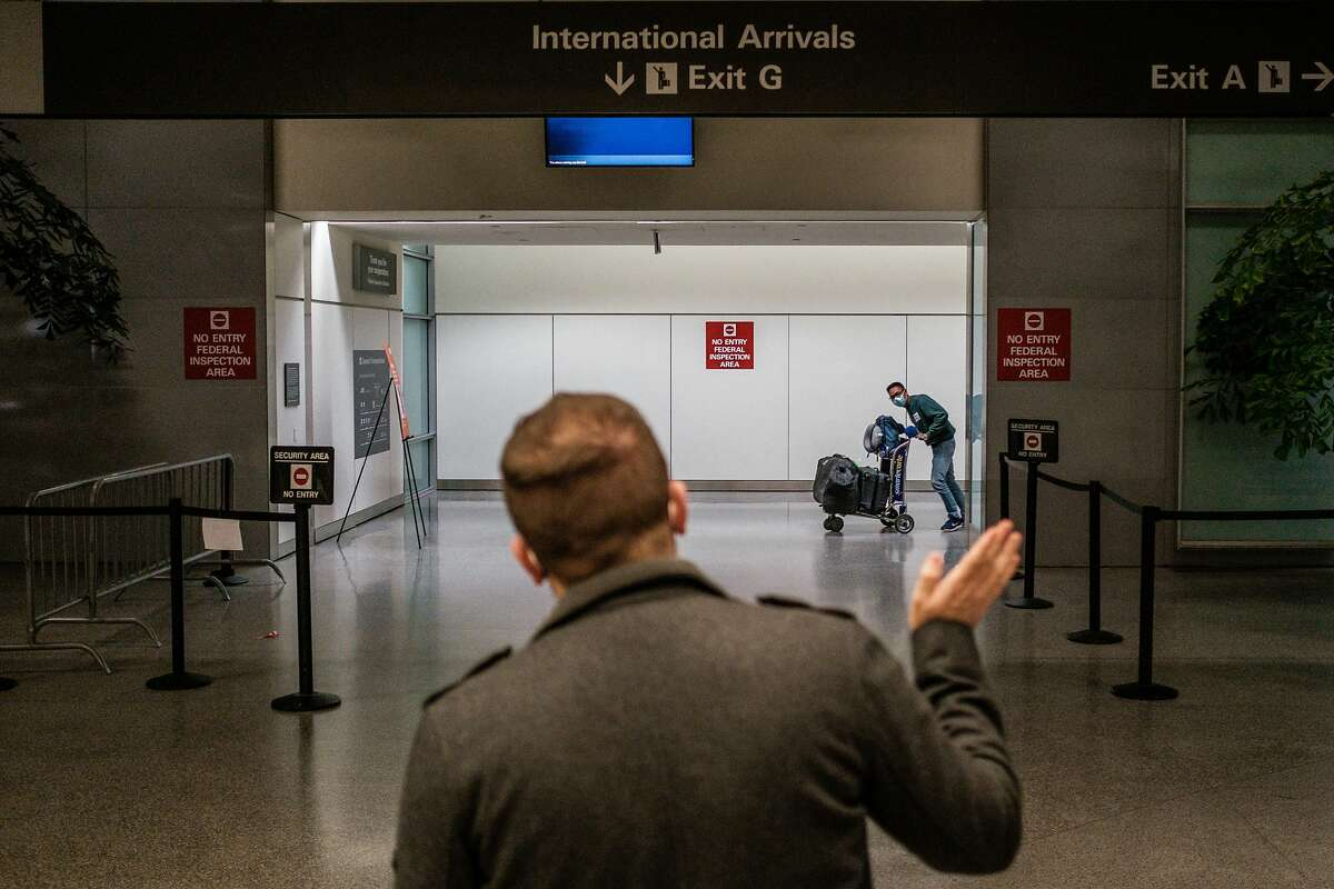 Kenny Kruse waves to fiance Yar Zar Min after the arrival of his flight at SFO in San Francisco.