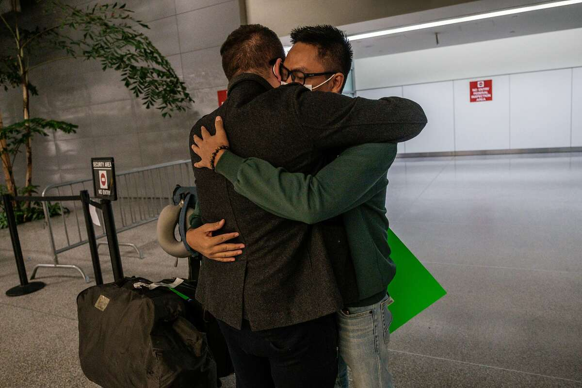 Kenny Kruse embraces fiance Yar Zar Min for the first time in two years after the arrival of his flight at San Francisco International Airport. Yar Zar Min received his fiance visa in late January. He had planned to move to San Francisco to be with Kruse, but a military coup in Myanmar froze his plans.