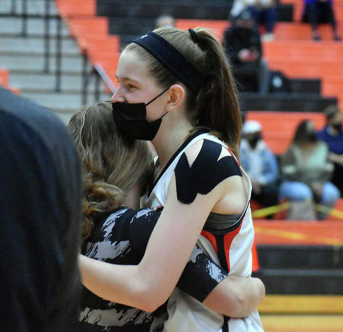 Edwardsville senior center Katelynne Roberts hugs coach Caty Happe after coming out of the game Thursday in her final regular-season home game inside Lucco-Jackson Gymnasium.