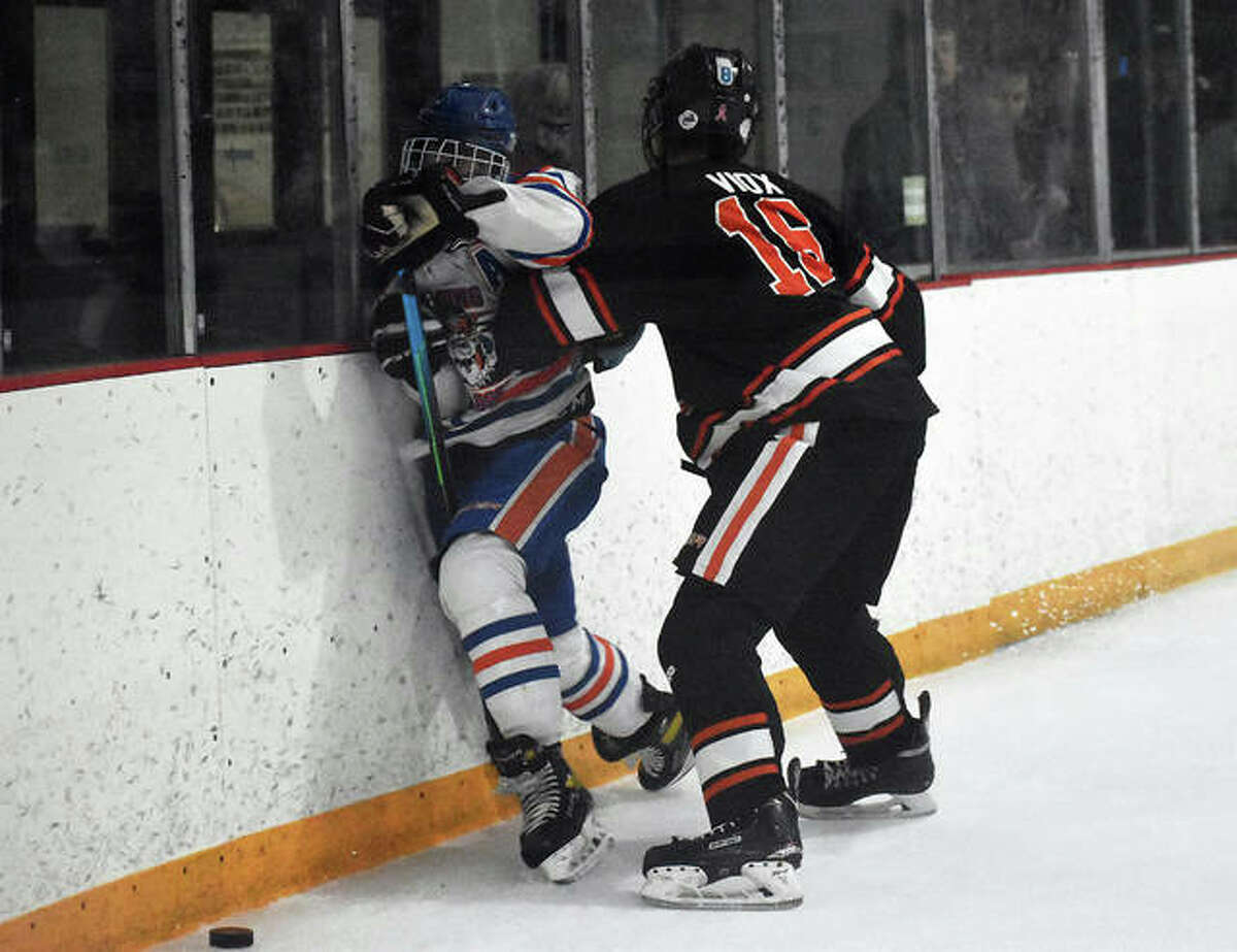 Edwardsville's Jospeh Viox levels his opponent against the boards during Thursday's game against Freeburg-Waterloo inside the East Alton Ice Arena.