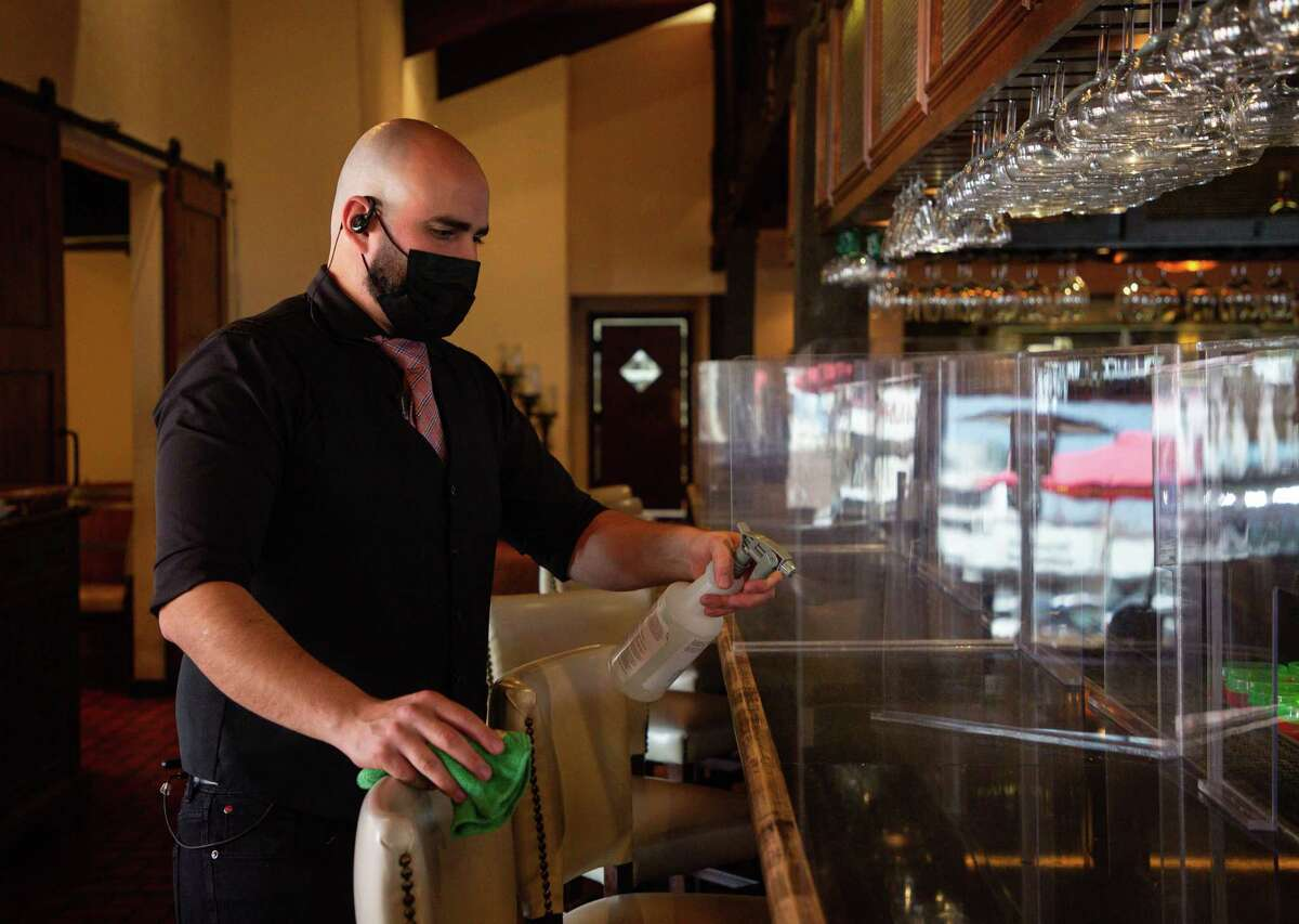Arnaldo Richard's Picos Restaurant bartender Daniel Vázquez sanitizes the countertop after customers left Thursday, March 4, 2021, in Houston. Following Gov. Greg Abbott's order lifting the statewide mask mandate and other COVID-19 restrictions, many Houston restaurants like Picos have vowed to keep those measures in place. Now they're getting threats.