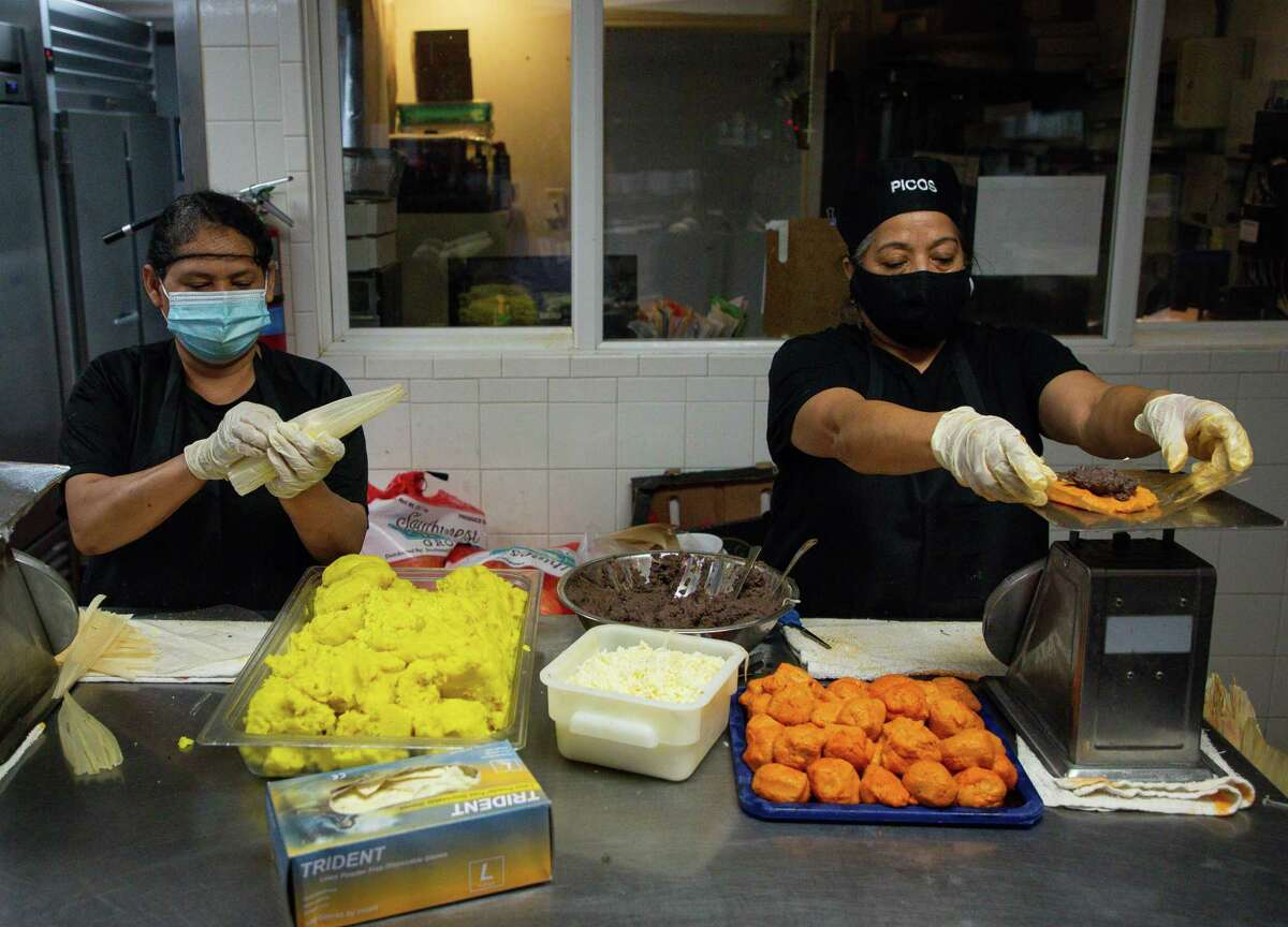 Caridad Gonzalez, left, and Magdalena Fonseca prepare tamales inside the Arnaldo Richard's Picos Restaurant kitchen on Thursday, March 4, 2021, in Houston. Following Gov. Greg Abbott's order lifting the statewide mask mandate and other COVID-19 restrictions, many Houston restaurants like Picos have vowed to keep those measures in place. Now they're getting threats.