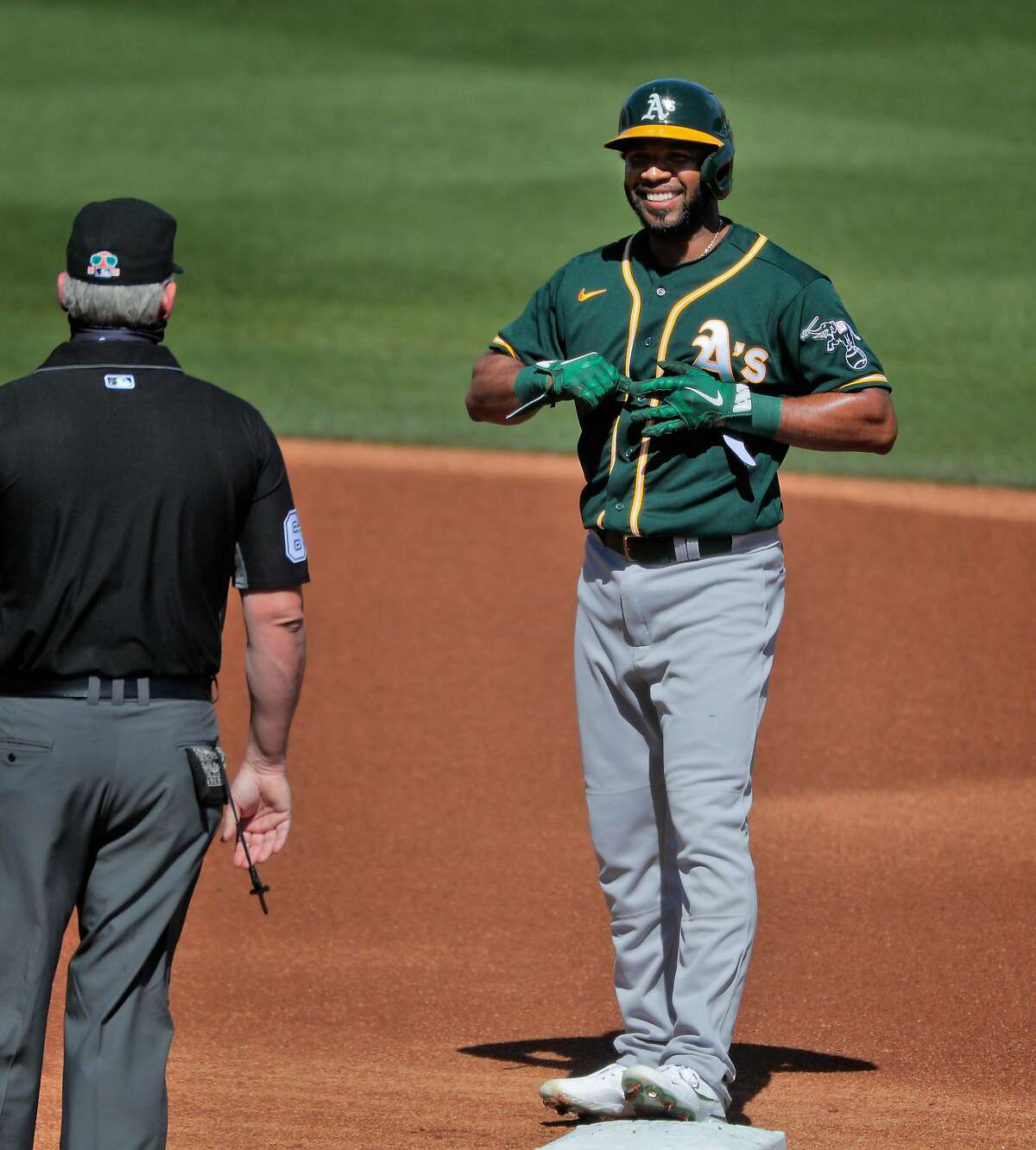 Elvis Andrus (17) smiles at second base umpire Jim Wolf in the first inning as the Oakland Athletics played the Colorado Rockies at Salt River Fields at Talking Stick in Scottsdale, Ariz., on Wednesday, March 3, 2021.
