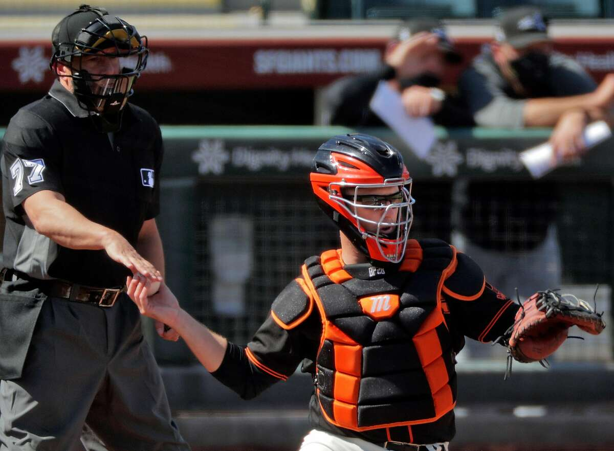 Buster Posey (28) gets a new ball from home plate umpire Jim Reynolds (77) in the second inning as the San Francisco Giants played the Chicago White Sox in a spring training game at Scottsdale Stadium in Scottsdale, Ariz., on Thursday, March 4, 2021.