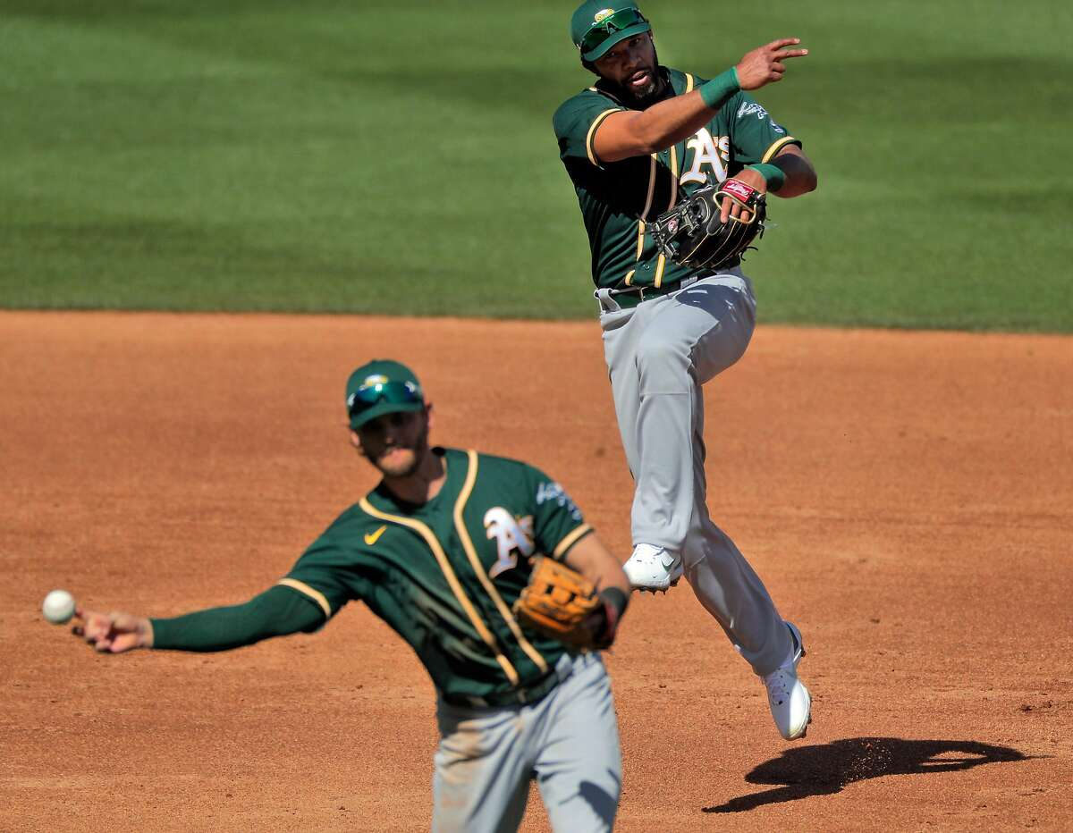 Double play? Elvis Andrus, back, mimics the throwing motion of teammate Chad Pinder during a March 3 game in Scottsdale.