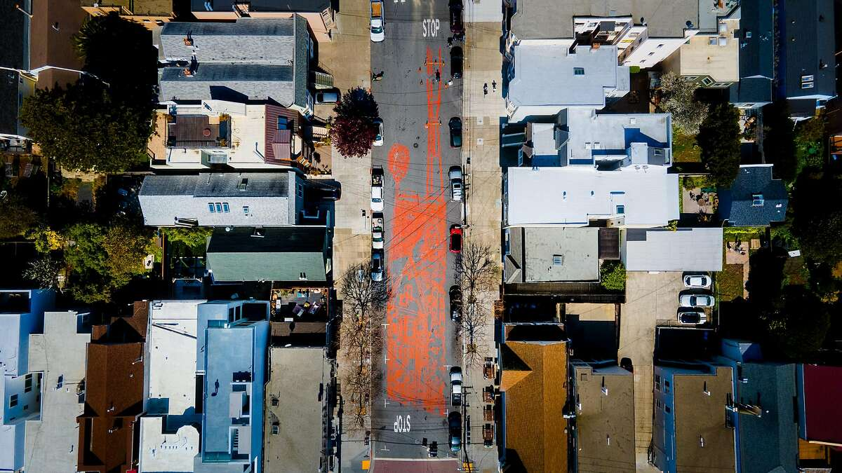 San Francisco artist Amos Goldbaum paints a mural on Sanchez Street between 24th and Elizabeth streets. The mural is a block long and is a depiction of San Francisco with Victorian houses and Sutro Tower.