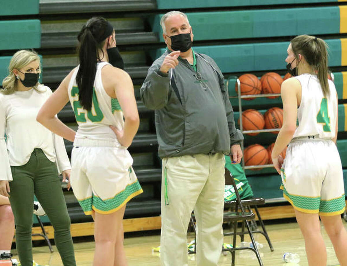 Southwestern coach Steve Wooley talks with Birds Korrie Hopkins (20) and Josie Bouillon (4), while assistant coach Jenna Wernsing listens in during a quarterly mask break in a Feb. 19 game vs. Pana in Piasa.