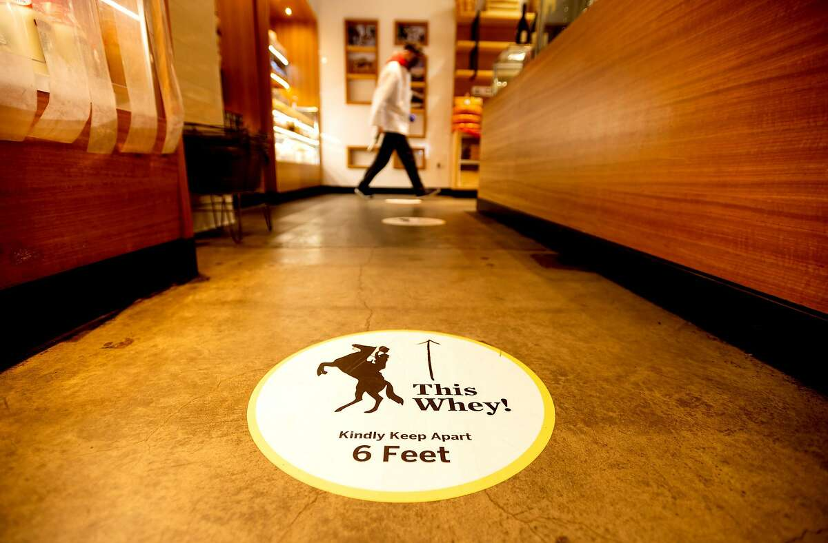 A floor sign at Ferry Building location of Cowgirl Creamery encourages social distancing.
