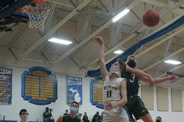 Pine River senior Garett Sumpter blocks a layup attempt by Evart sophomore Gavin Simmer during the Bucks' 66-38 victory over the Wildcats on Thursday night at Evart High School. (Pioneer photo/Joe Judd)