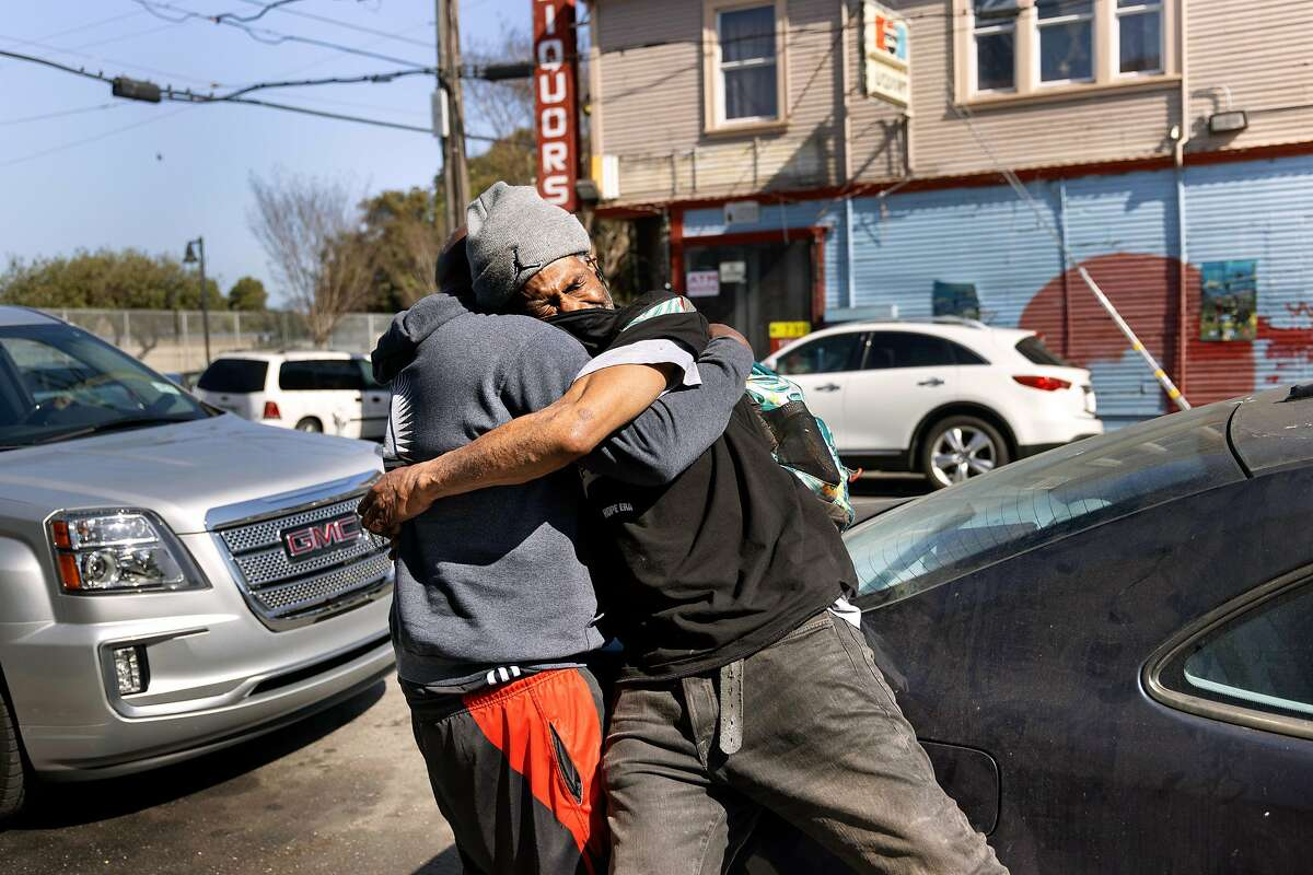 """Demetrius """"Hook"""" Mitchell (right) hugs former basketball student, Skyline High coach DeUndrae Perteete, in West Oakland. Mitchell is admired by NBA Hall of Famers with Oakland roots, Jason Kidd and Gary Payton."""