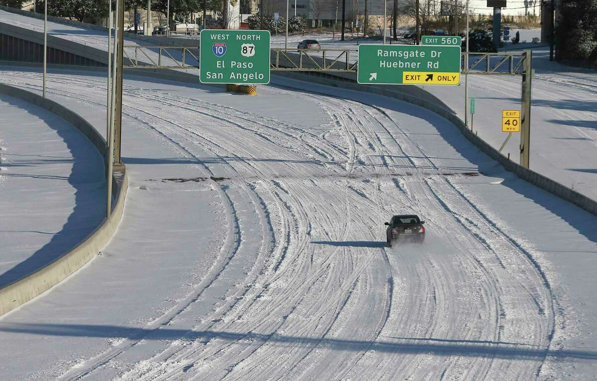 A vehicle drives on IH-10 westbound on Monday, Feb. 15, 2021. Several inches of snow fell in the city from Sunday, Feb. 14, starting in the evening through the early morning hours of Monday, Feb. 15, 2021. A few vehicles and people were out either to see the spectacle or to try to head to work.