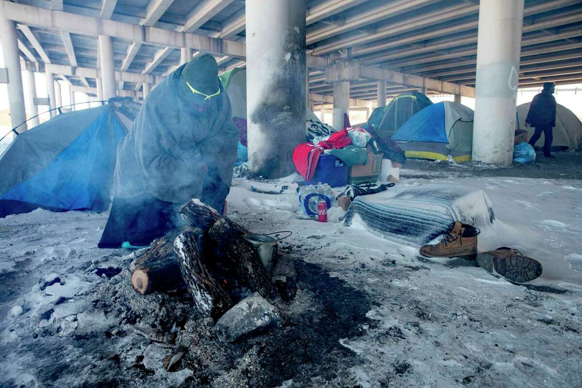 A man who goes by the name of Snipe tries to warm himself by the fire outside tents in a campsite for the houseless under the 37 underpass on February 15, 2021. Snipe and many other homeless stayed in tents overnight even as temperatures dropped to dangerous lows.