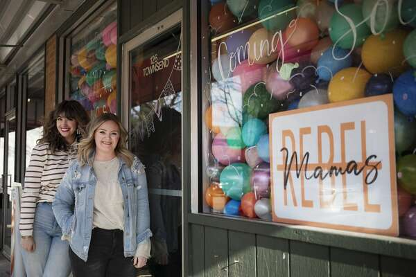 From left, Mackenzie Hopkins and Kaela Dolan pose for a portrait Wednesday, March 3, 2021 in front of Rebel Mamas, their new event and party business in downtown Midland. (Katy Kildee/kkildee@mdn.net)