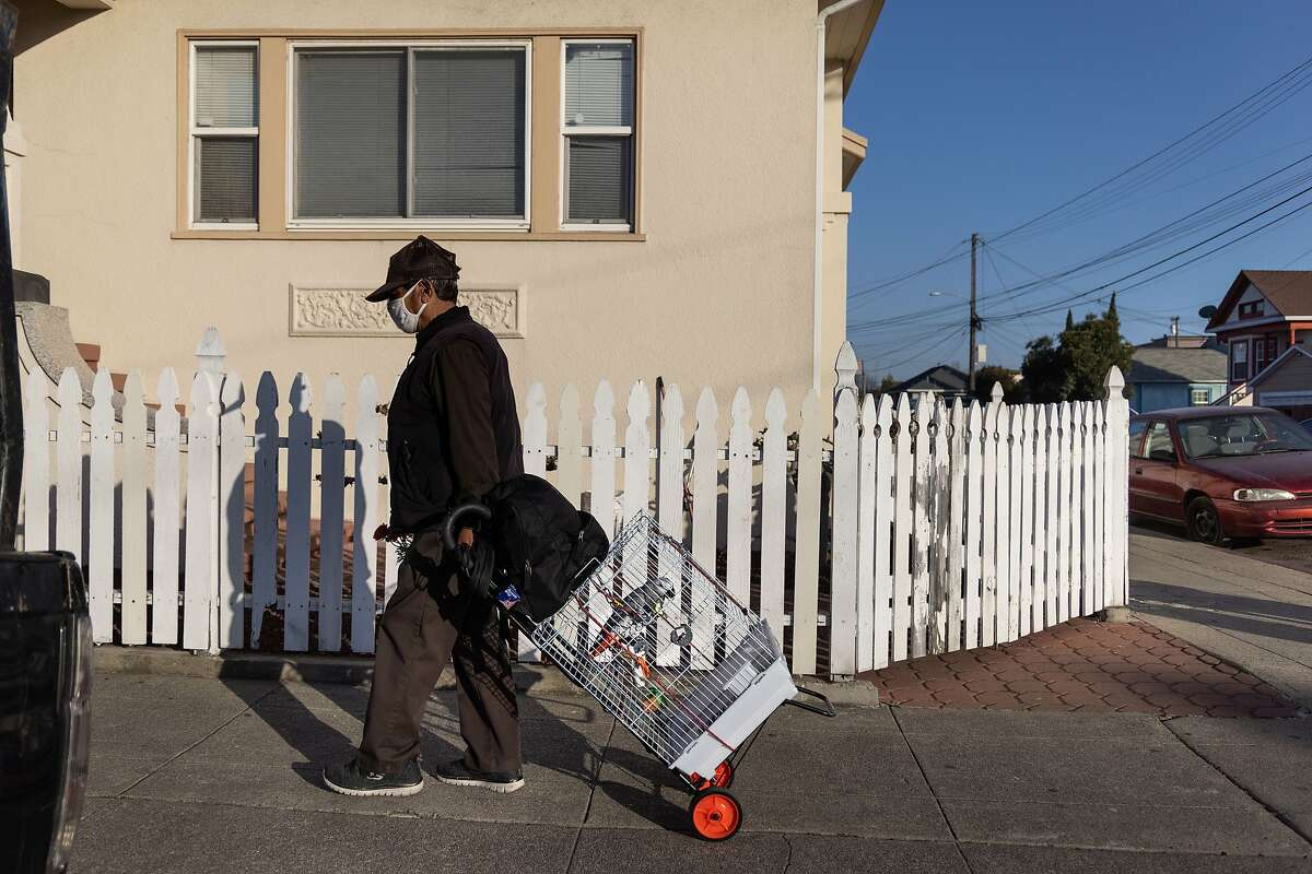 Juan Elvira, 71, moves his African Grey Parrot named Shakira in the Fruitvale District on Thursday, March 4, 2021 in Oakland, Calif. The state recently announced that it's now prioritizing certain zip codes for the vaccine.