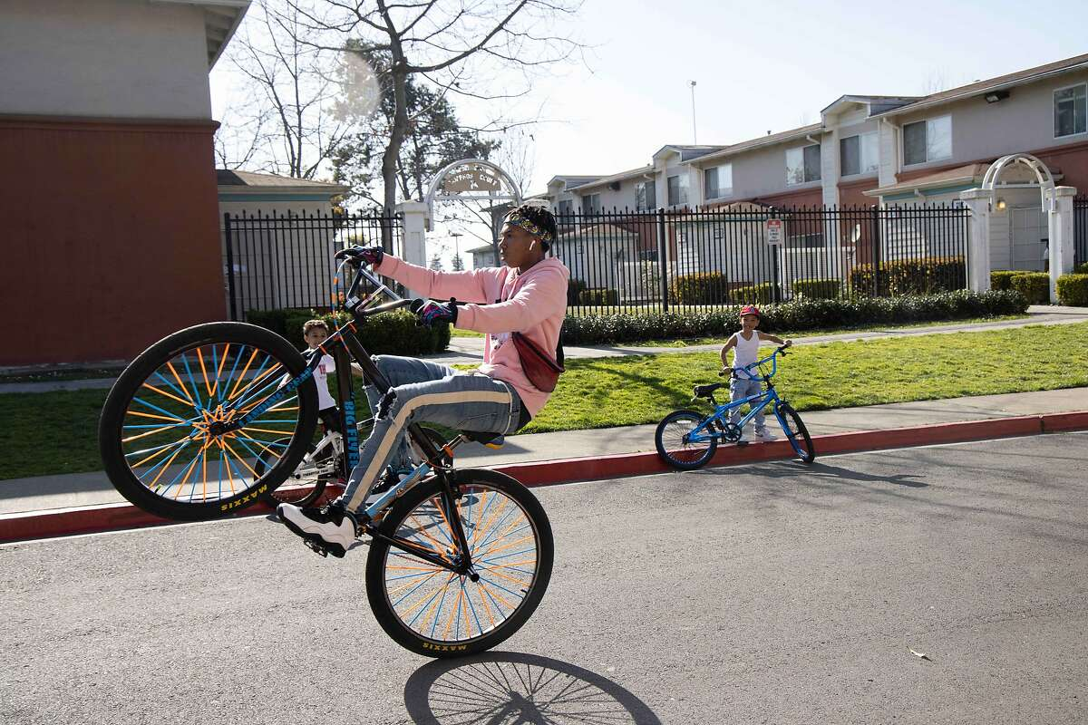 A boy on a bike does a wheelie at an housing complex near the RingCentral Coliseum on Thursday, March 4, 2021 in Oakland, Calif. The state recently announced that it's now prioritizing certain zip codes for the vaccine.