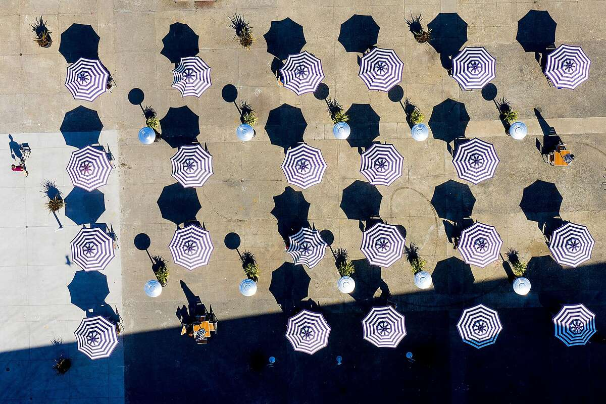 Umbrellas cover tables at an outdoor seating area behind the Ferry Building.