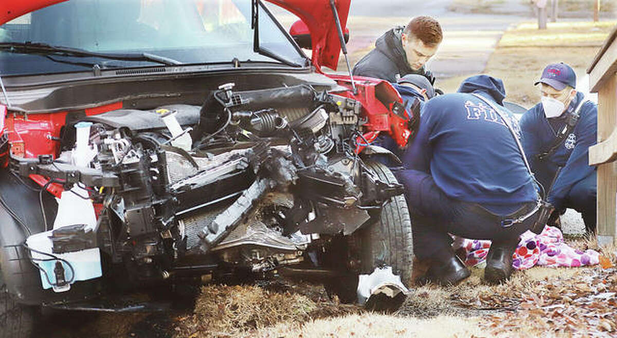 Alton firefighters huddle around the injured female driver of a Kia Soul early Monday morning following a head-on crash with a Ford Taurus in the 1100 block of Brown Street in Alton that sent both drivers to area hospitals.