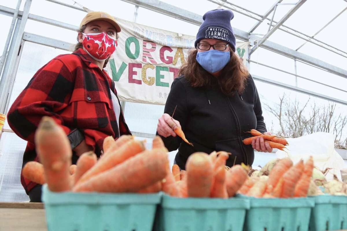 Mackenzie Brant, left, and Laura Markowicz, of Riverbank Farm of Roxbury, one of the original vendors at the Westport Farmers' Market on Thursday, March 4, 2021, in Westport, Conn.