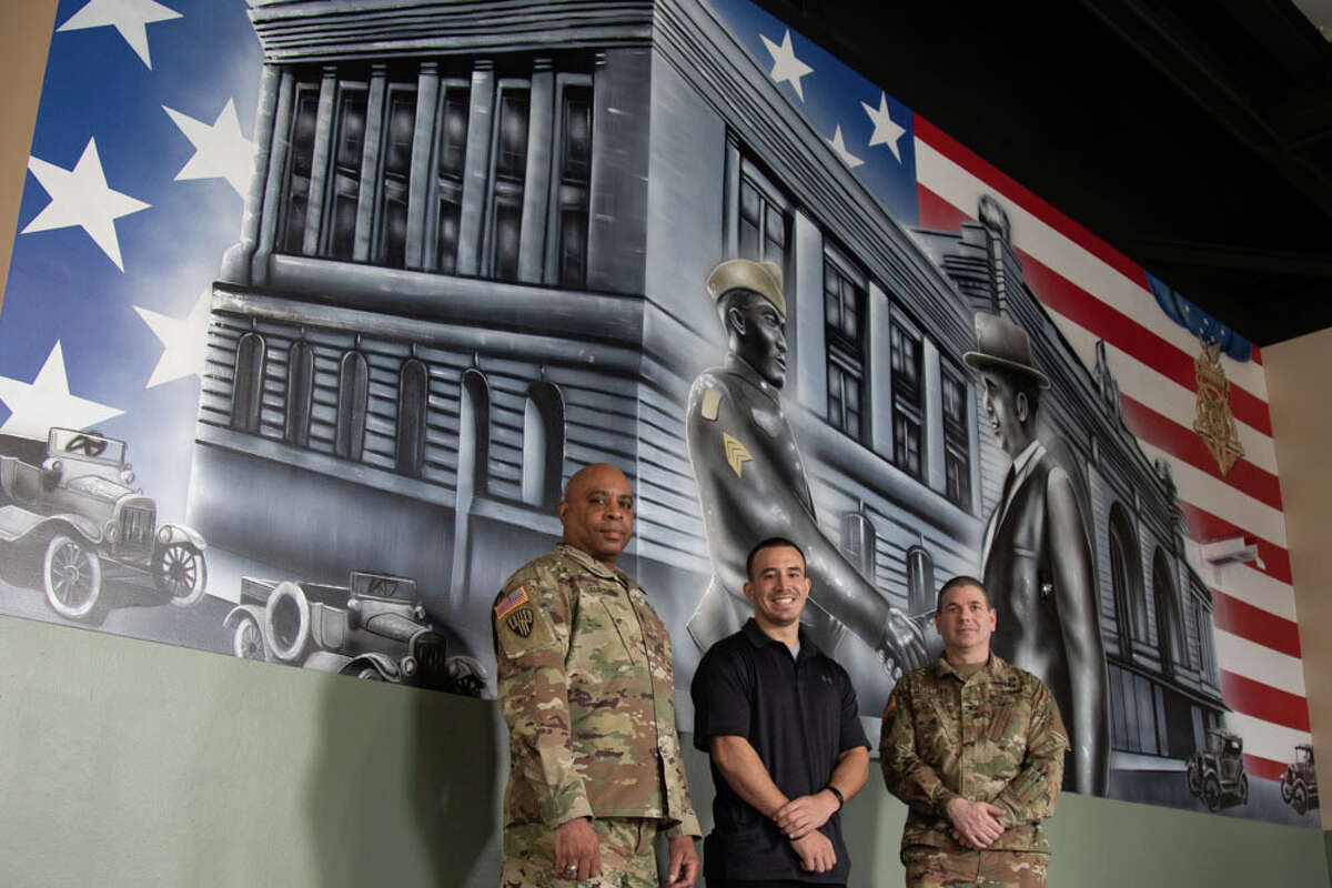New York Army National Guard Command Sgt. Maj. Andrew H. Lampkins, the Command Sgt. Maj. of the 369th Sustainment Brigade and Col. Seth L. Morgulas, Commander of the 369th Sustainment Brigade pose with Christopher Rios, artist of the Sgt. Henry Johnson mural, at Camp Smith Training Site on February 26, 2021. The mural dedicated to Sgt. Henry Johnson, Medal of Honor recipient, who fought with the 369th Infantry in World War I, decorates the newly modernized Simulations Training Building at Camp Smith. (U.S. Army National Guard photo by Spc. Angela Minardi)