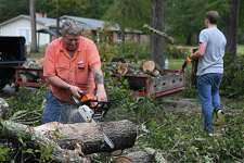 Rhett Borg, right, helps Michael Whitt remove trees Thursday that were knocked down at his Hardin County home during Tuesday's storm. Whitt said seven trees fell in his yard. Photo taken Wednesday, 10/30/19