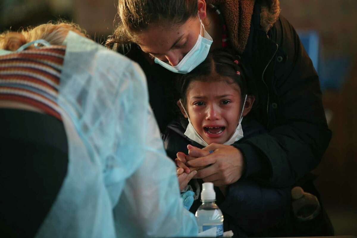 A young girl cries as her finger is pricked to test blood for COVID antibodies at a Brownsville bus station last month.