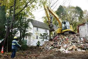 Crews demolish the blighted house at 46 Mead Ave. in the Byram section of Greenwich, Conn. Tuesday, Nov. 19, 2019. The town was inspired to set up new ordinances for dealing with blighted properties after this case.