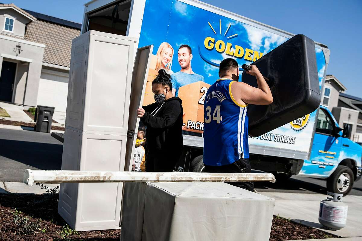 Shellane Calixto holds a door panel as husband Ralph delivers a furniture component to her sister-in-law at the planned community at River Islands in Lathrop.