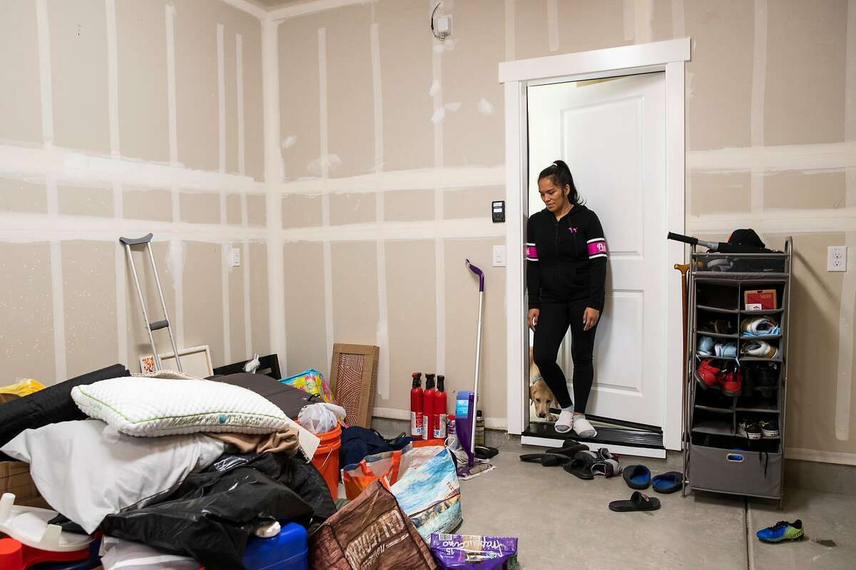Bing Banaag looks at a pile of unpacked belongings in the garage of her home at the planned community at River Islands in Lathrop. The Banaag family moved from Hercules to Lathrop in February.