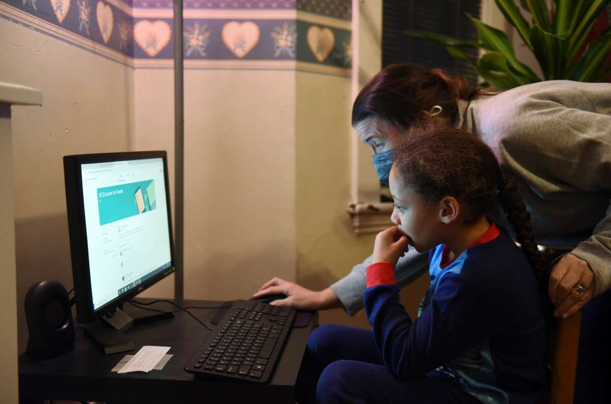 Mary Taylor, right, helps her son, Aarmani, 4, who attends Delaware Community School, on a computer donated by the Albany Fund for Education on Wednesday, Dec. 9, 2020, at their home in Albany, N.Y. The Albany School District is facing a four-month delay on its order of Chromebook computers for students. (Will Waldron/Times Union)